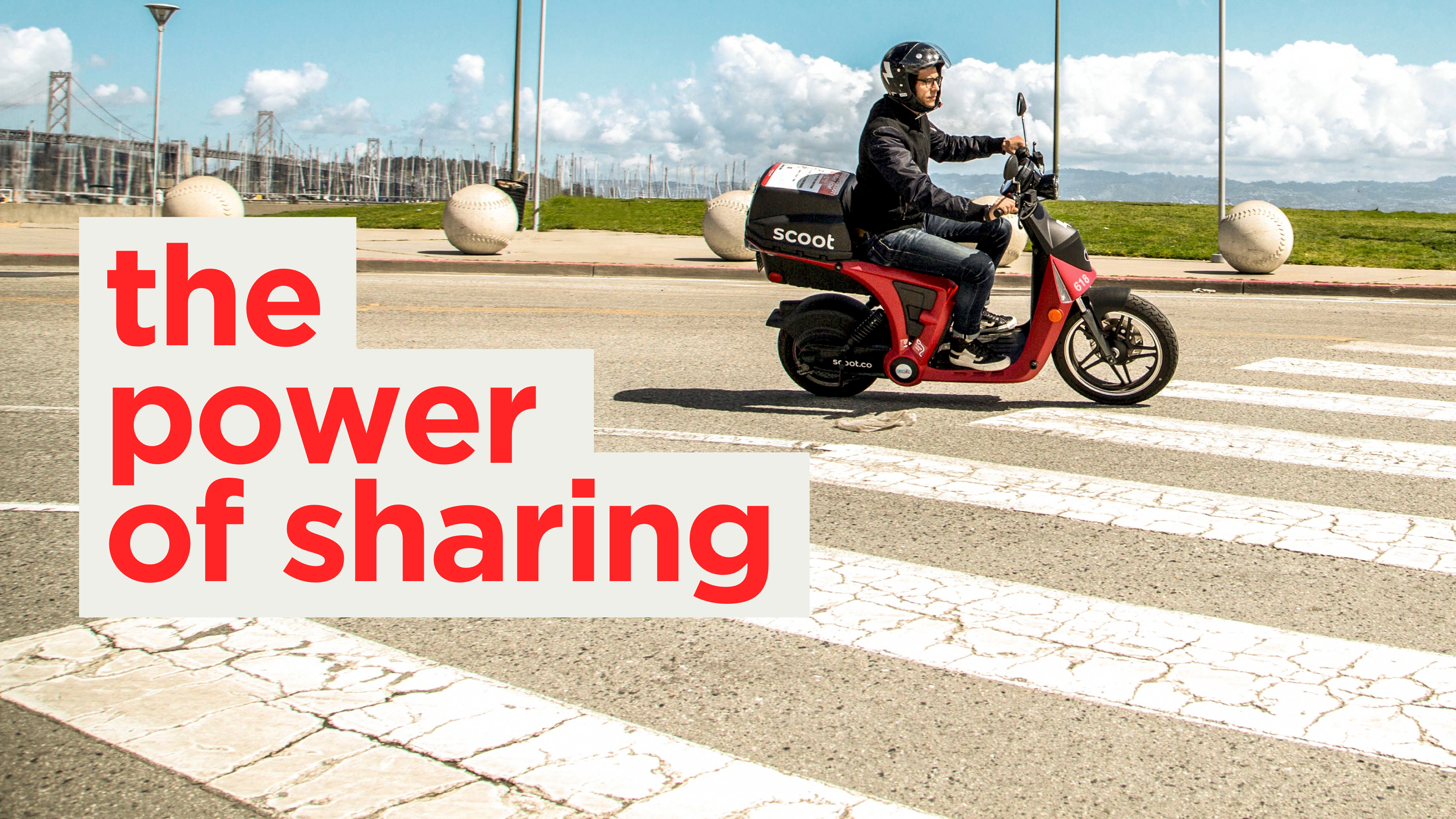 """A person making a slight turn on a scooter with typography stating """"the power of sharing"""" imposed on top of the image"""
