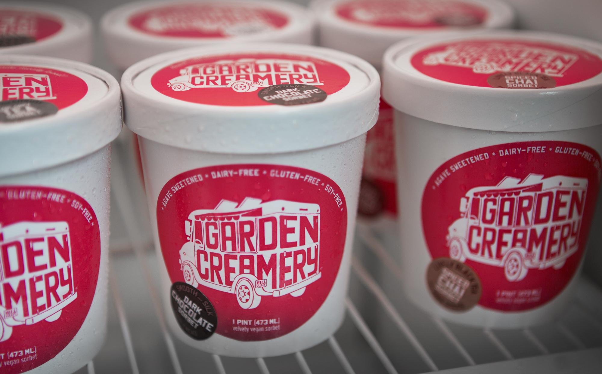 Several Garden Creamery ice cream pints stacked on freezer store shelf