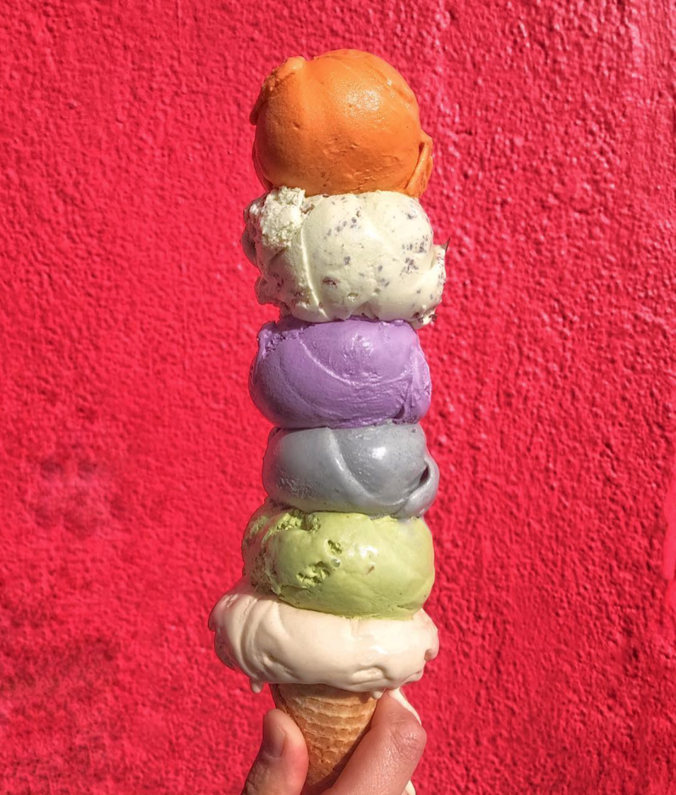 Six scoops of colorful icecream flavors on ice cream cone with strong pink background of Garden Creamery wall