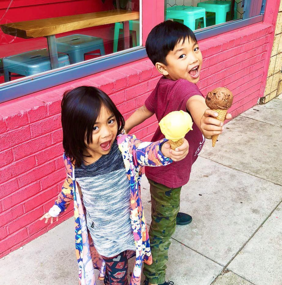 Two kids holding up ice-cream cones with happy faces out side of Garden Creamery