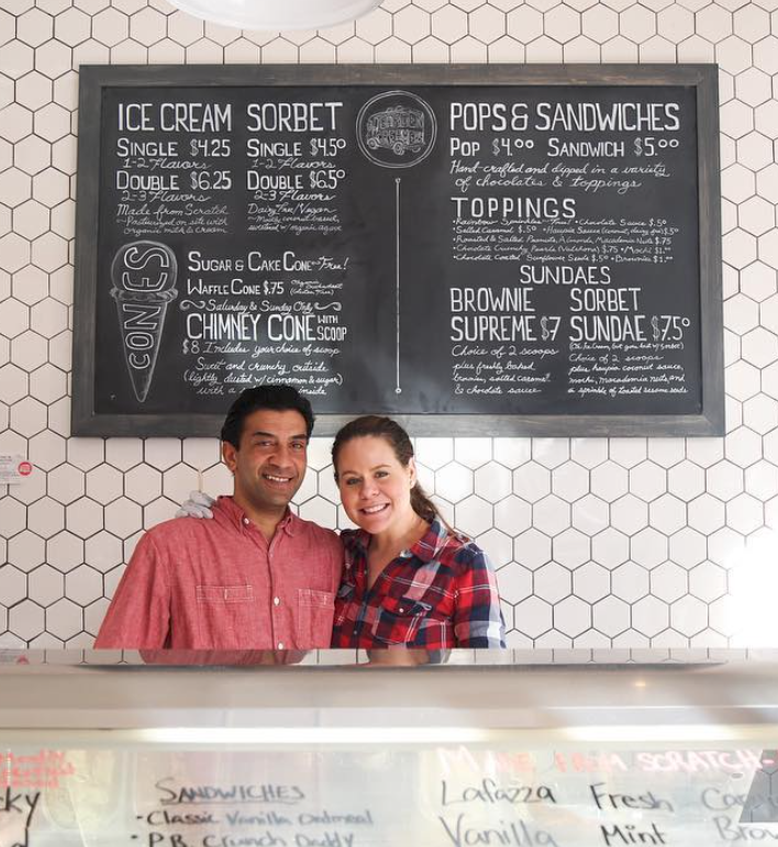 A man and women embracing behind ice cream counter at Garden Creamery