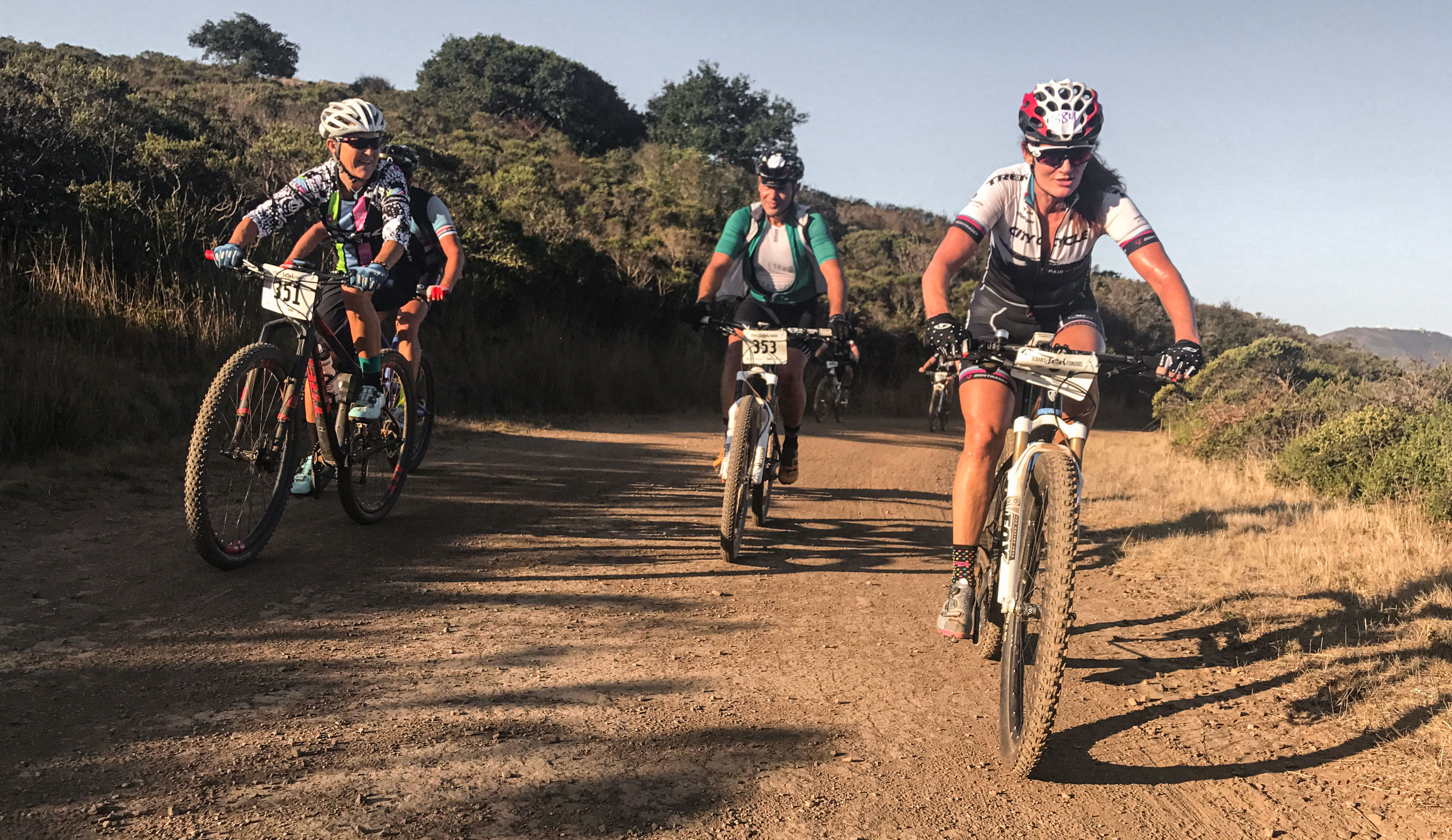 A big group of mountain bikers taking riding on a dirt trail at Dirt Fndo event