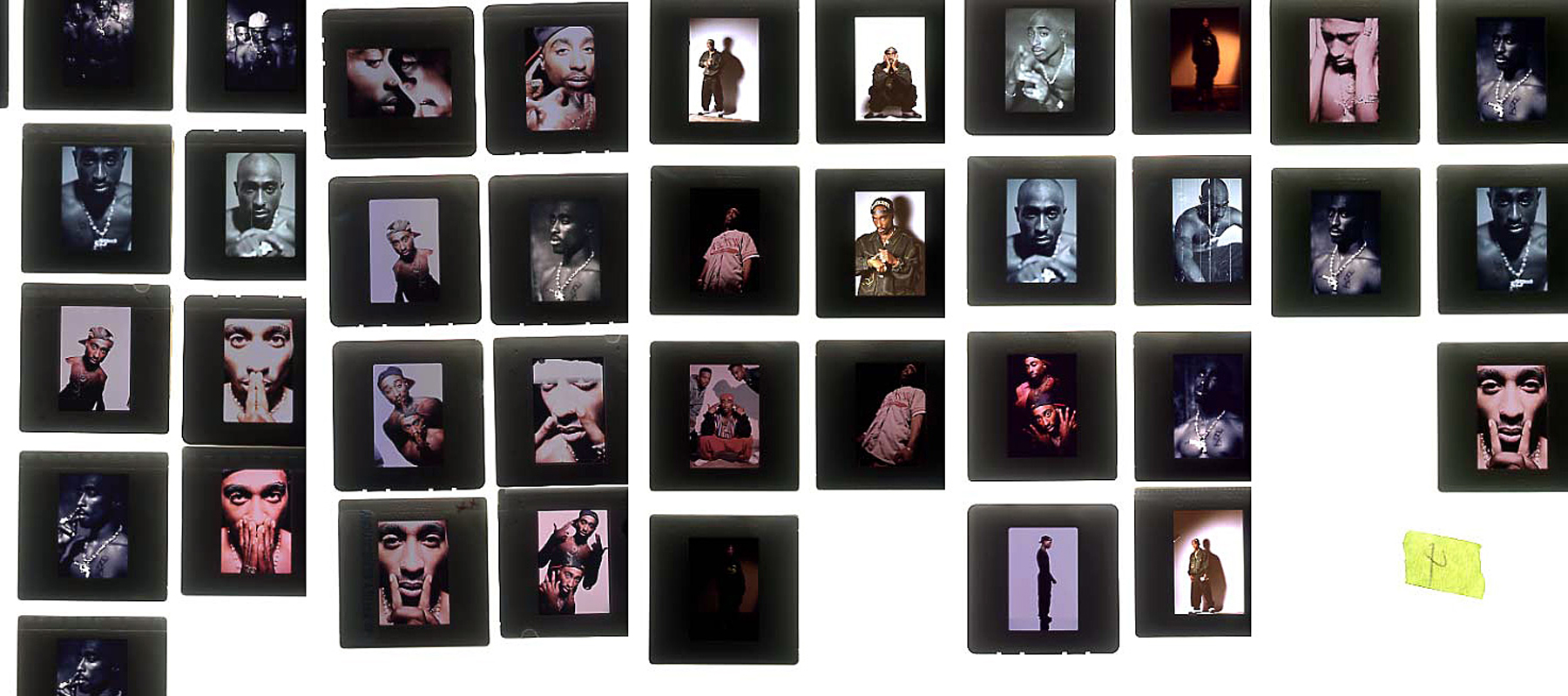 Many dramatic portraits of Tupac Shakur arranged on light table