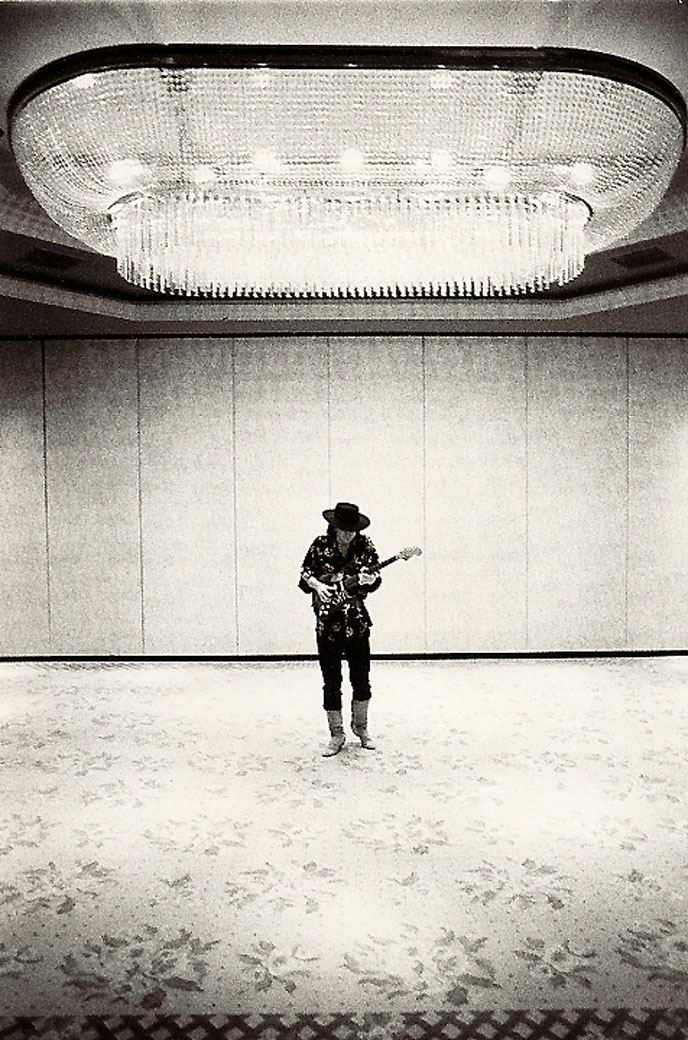Image of a man playing guitar under a giant chandelier