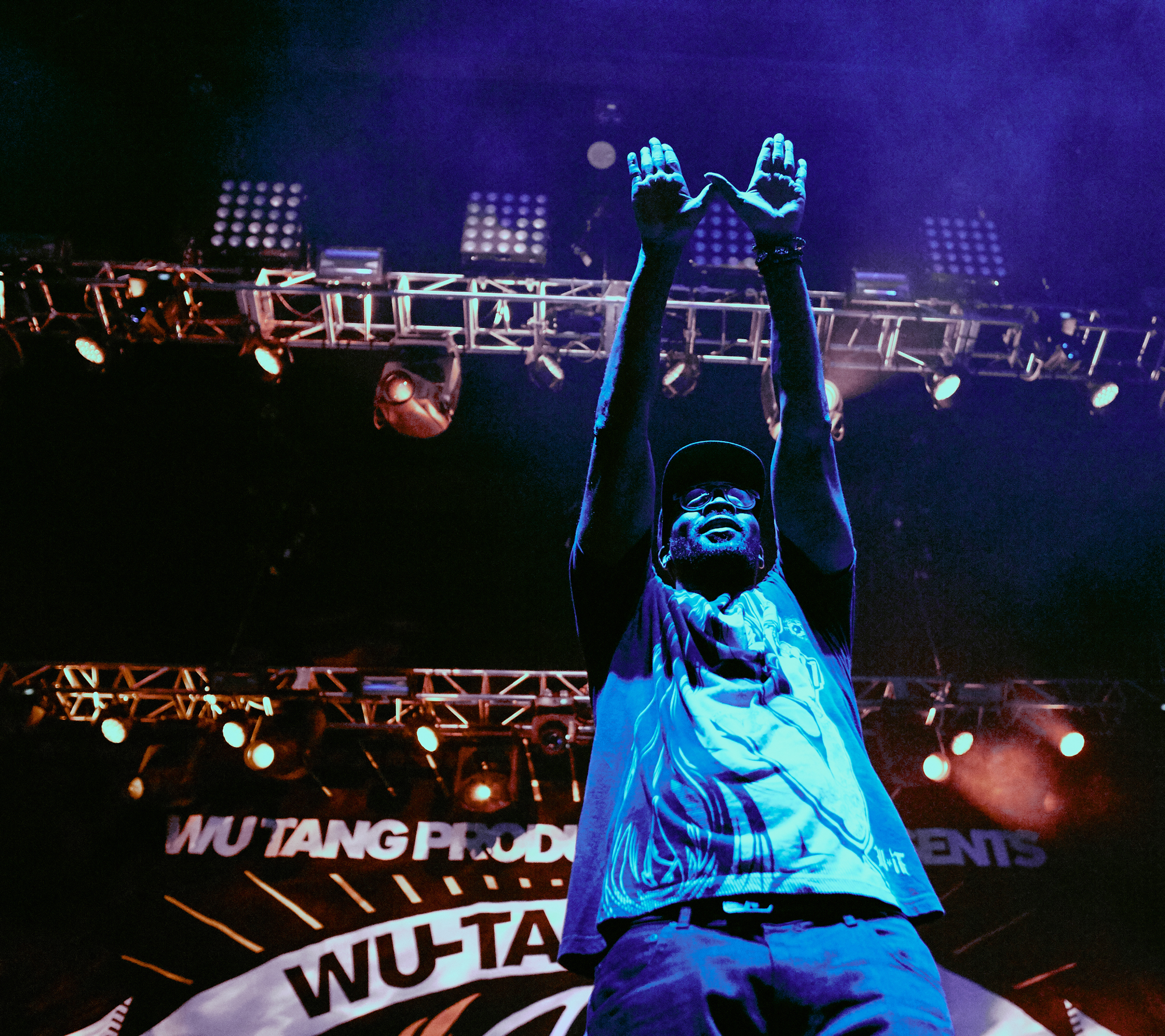 RZA holding up WU-TANG hand symbol will performing live at a concert