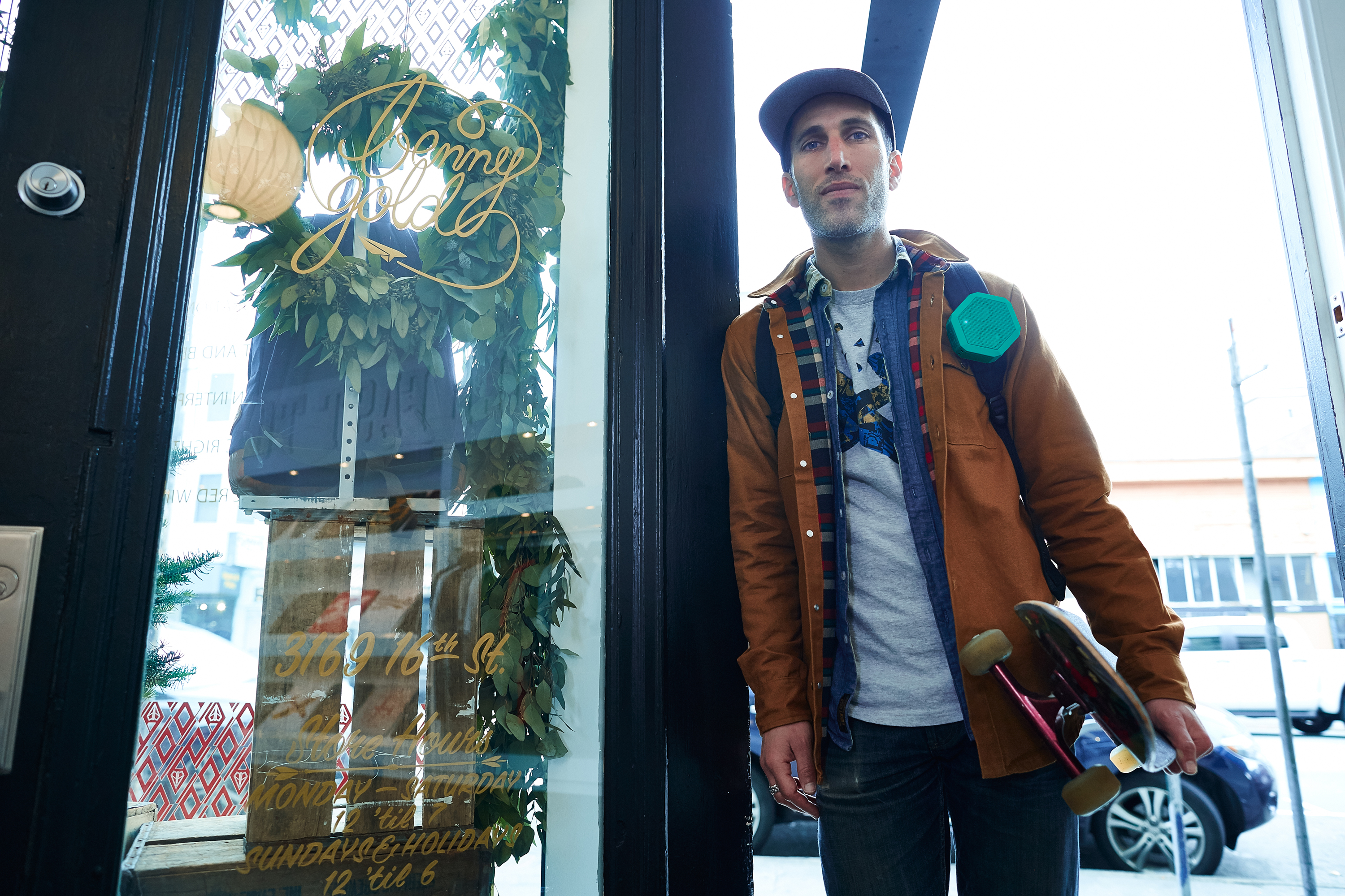 Benny Gold standing in storefront doorway with boombotix speaker strapped to backpack
