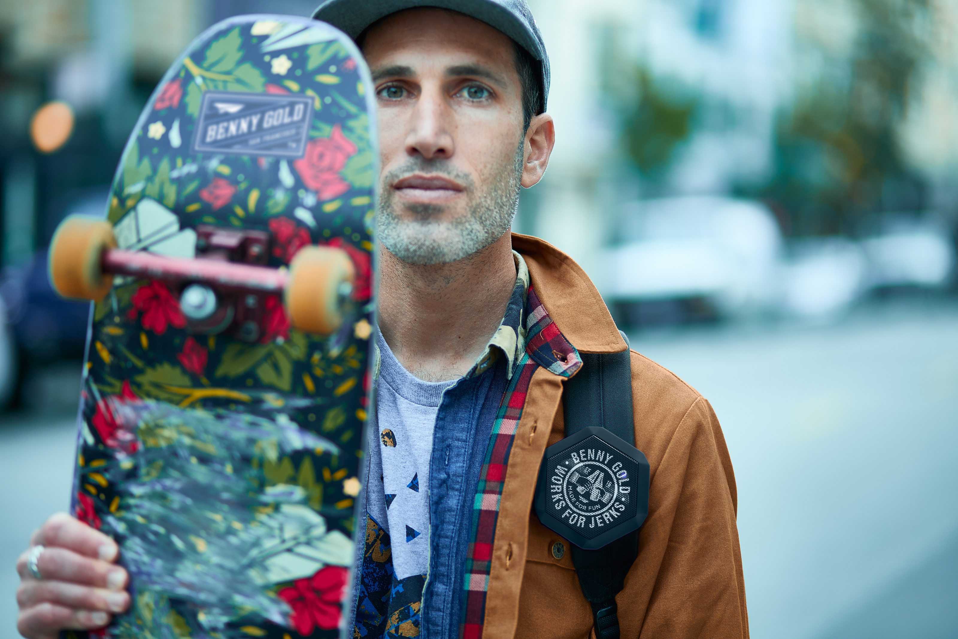 Benny Gold holding up skateboard and has boombotix speaker strapped to backpack