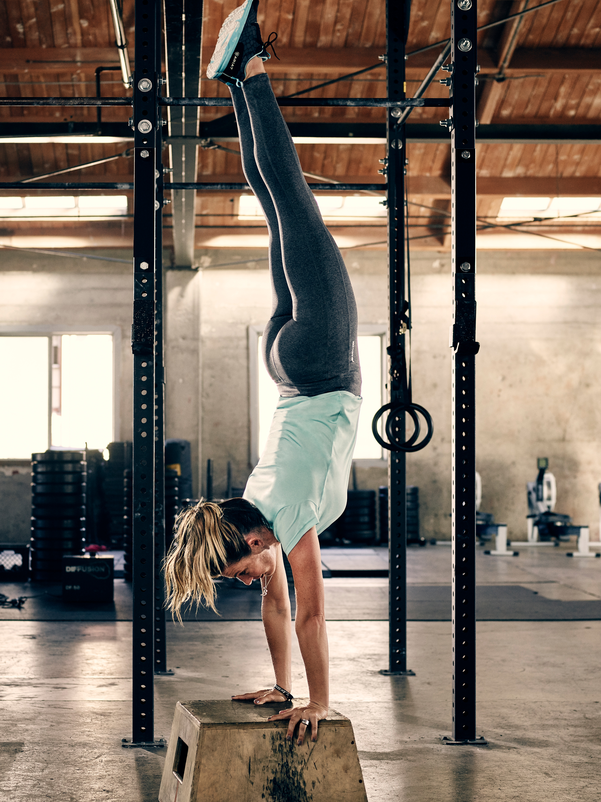 Women in gym working out, doing a handstand in Airat workout gear