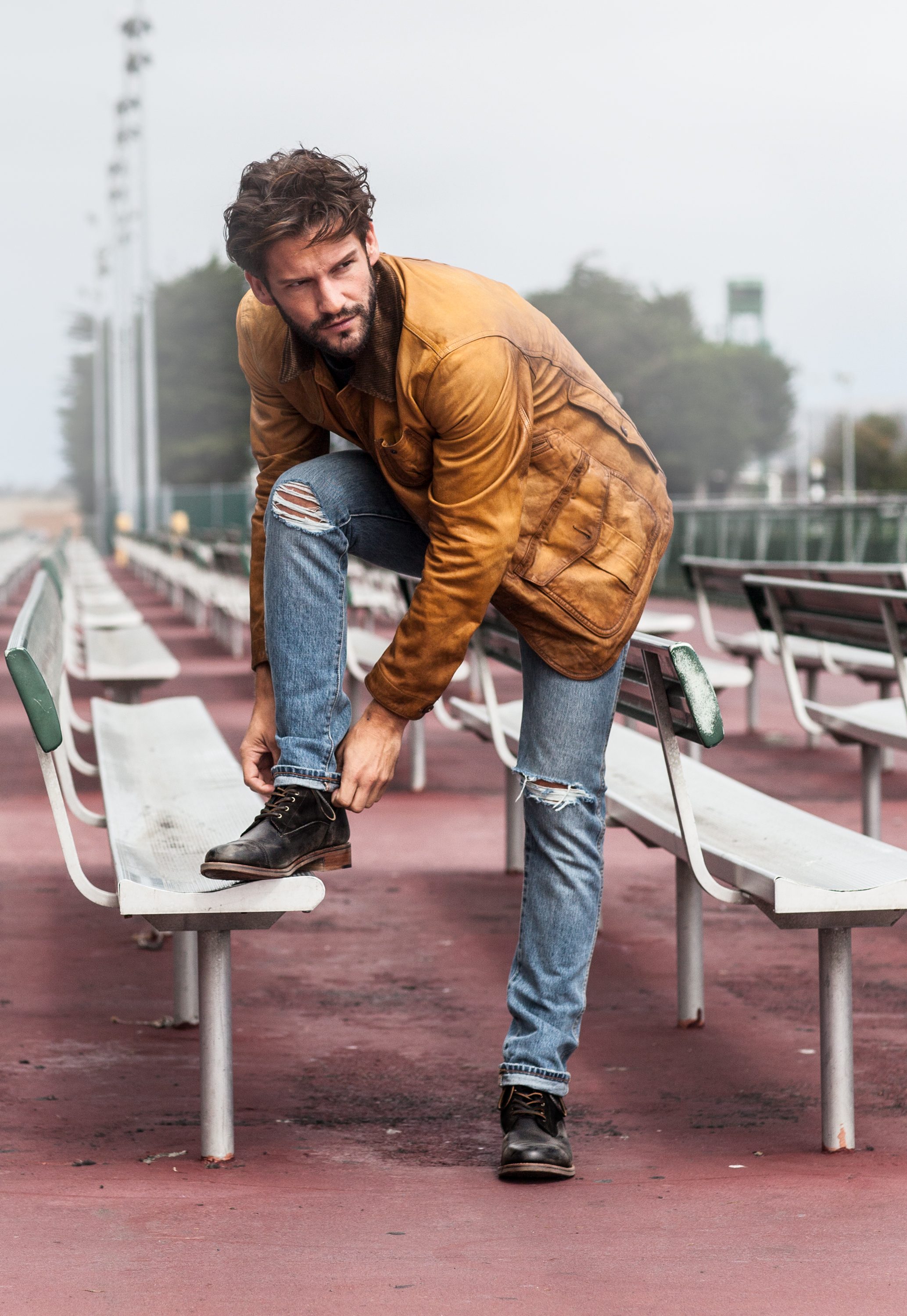 Man modeling and adjusting fashionable Ariat Two 24 boot on bleacher seat