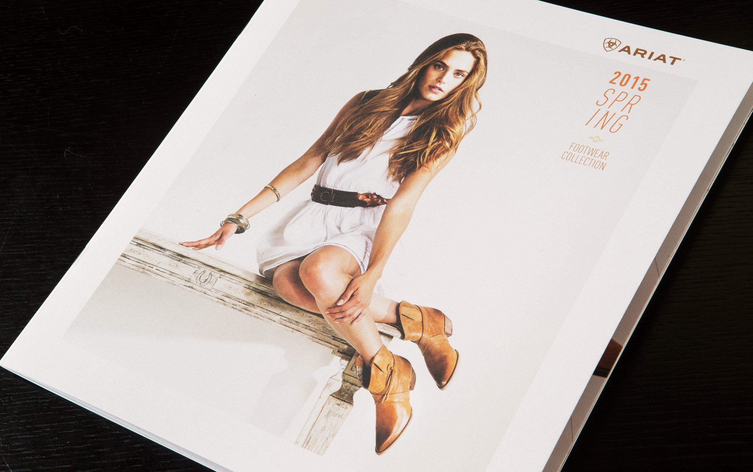 Ariat fashion look book cover with woman on table wearing equestrian inspired boots