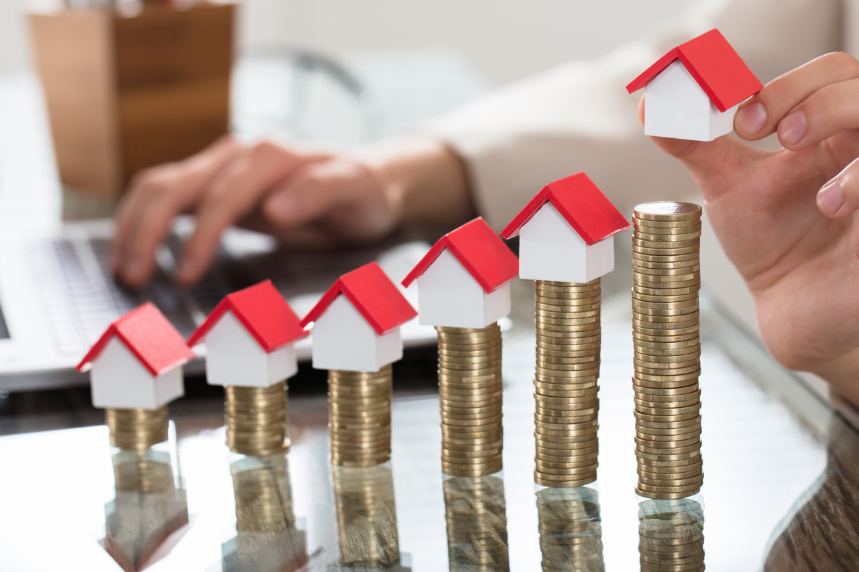 Mini houses on rising stacks of coins. Credit: iStock.com/AndreyPopov