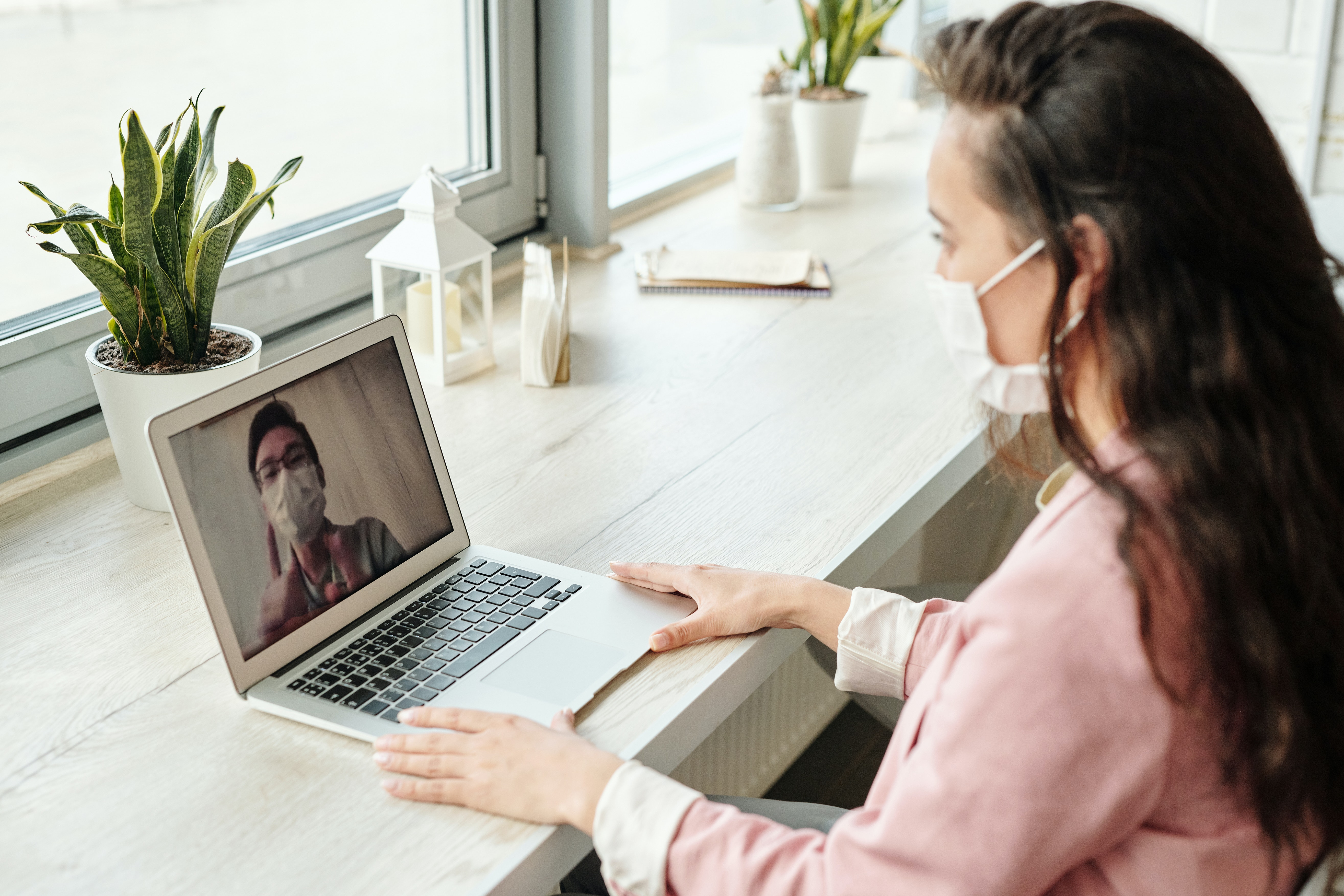 Woman on her laptop at home with a face mask.