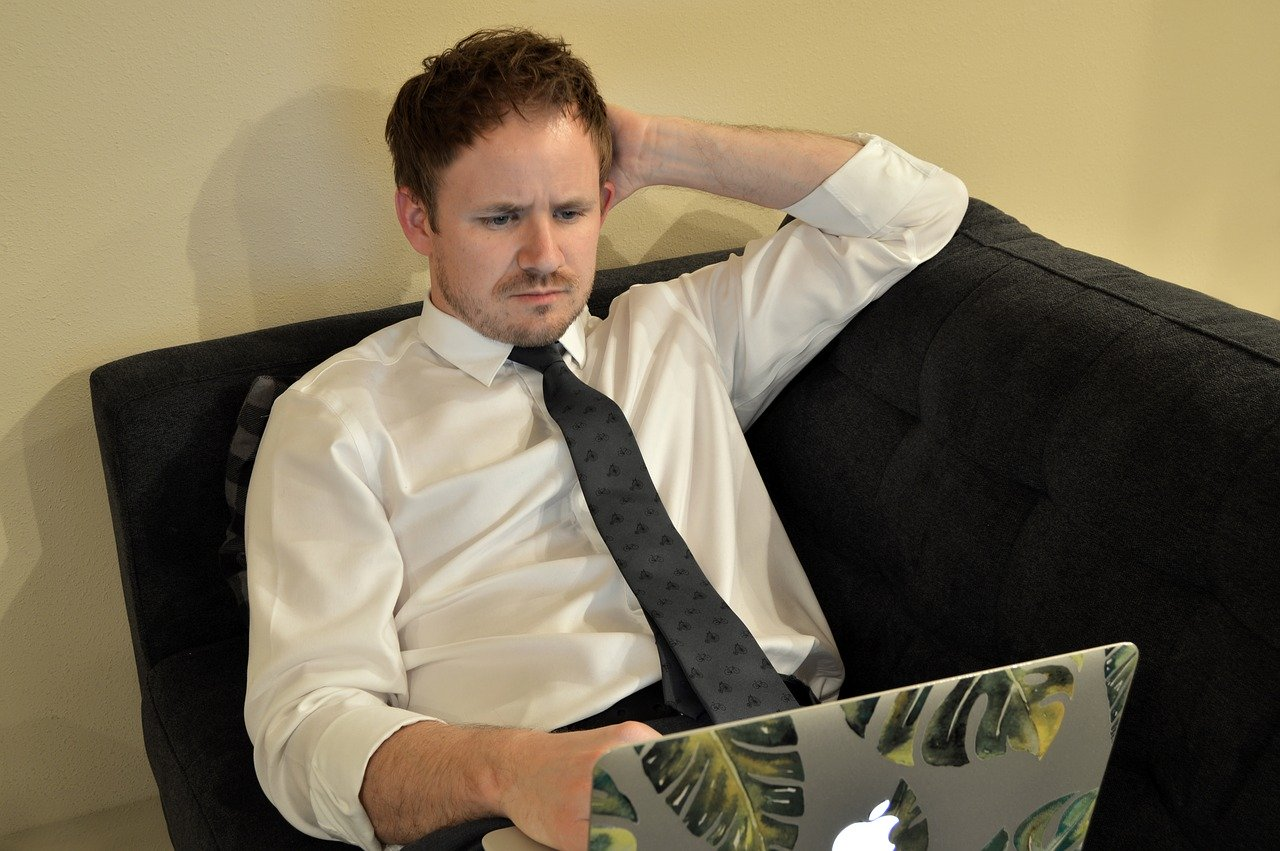 Man looking confused while staring at his computer.