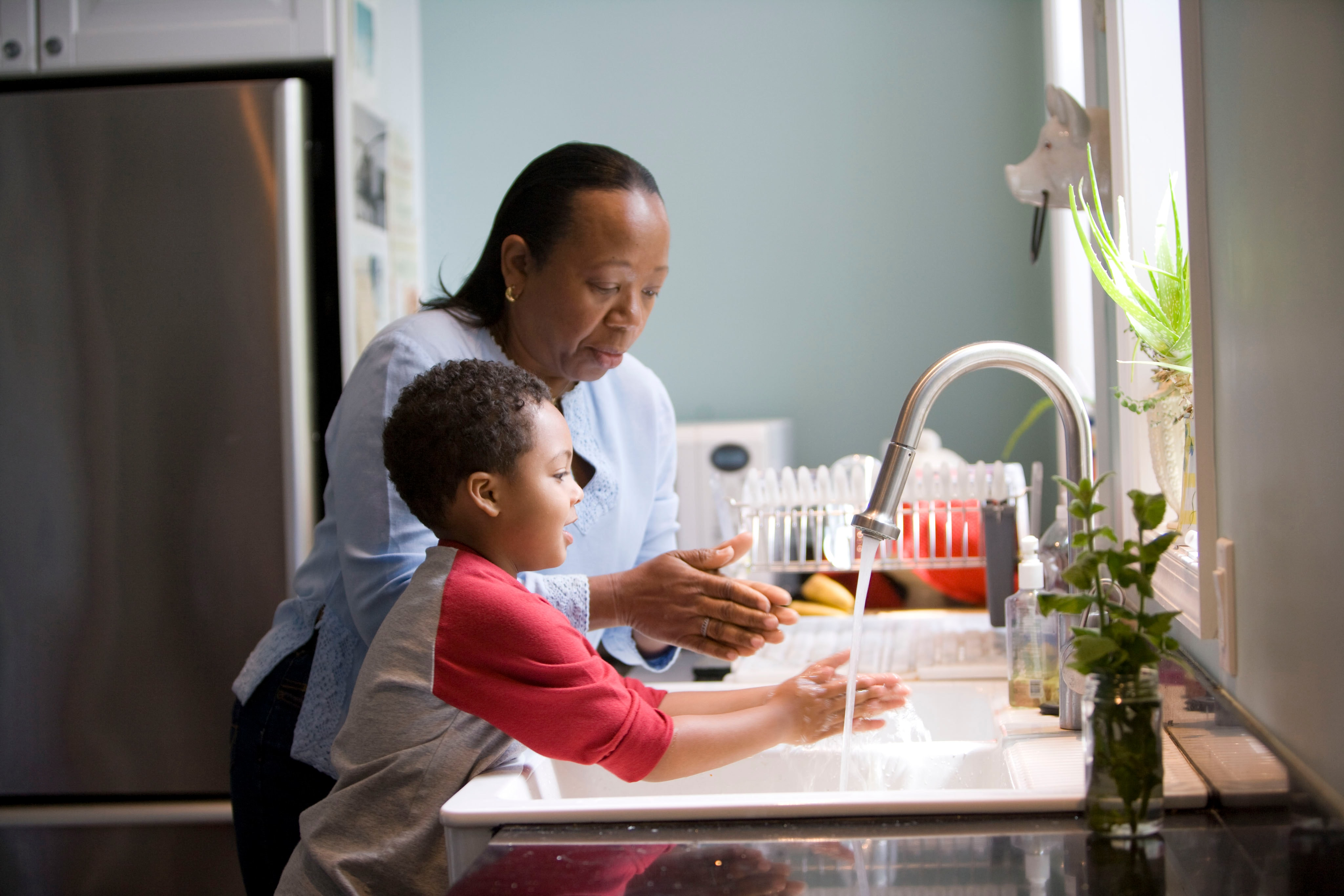 Black mother and son at a sink | Photo by CDC on Unsplash