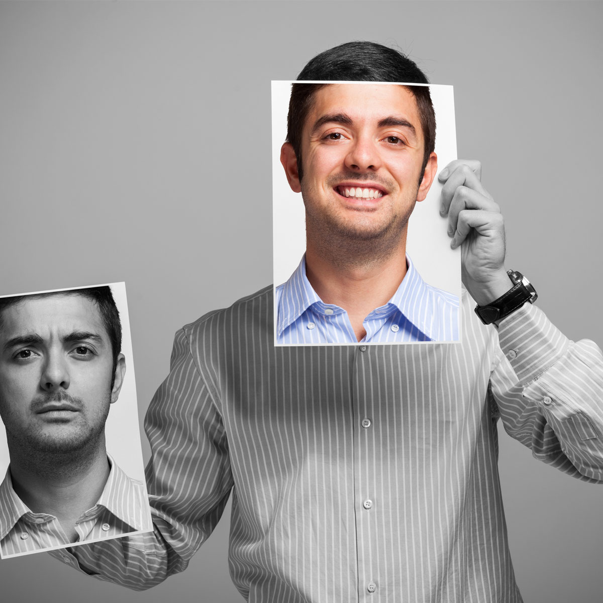 Man holding a smiling photo of his face in front of his face.