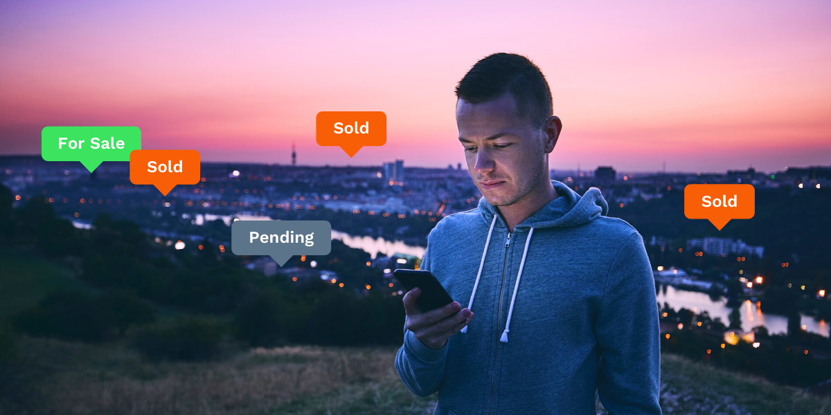 "Man looking at his phone with a distant town in the background, bubbles reading ""for sale,"" ""pending,"" and ""sold"" hover over the landscape."