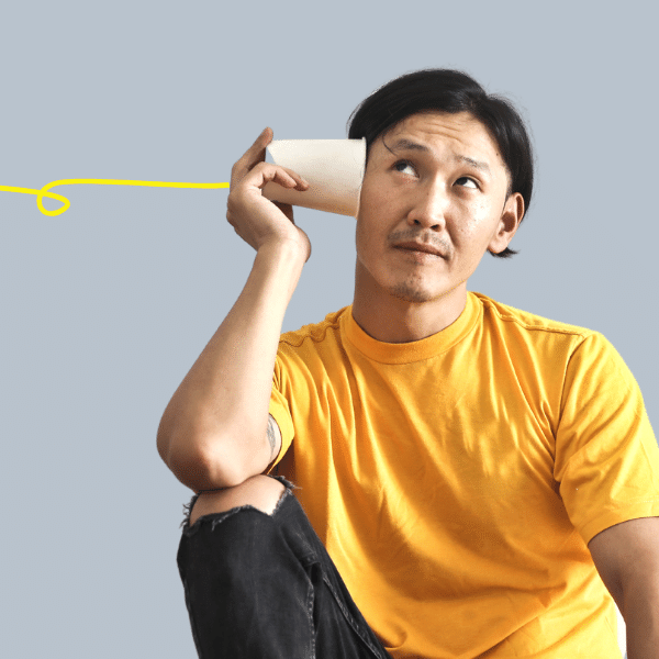 "A man in a yellow shirt is holding a paper cup ""phone"" up tp his hear with the cord trailing out of the frame"