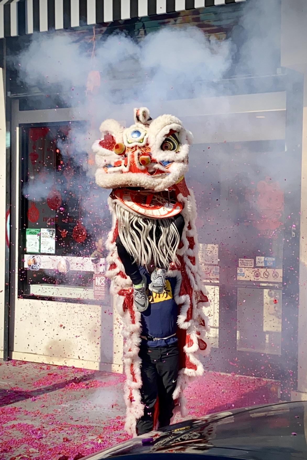 Lion Dancers perform under exploding firecrackers