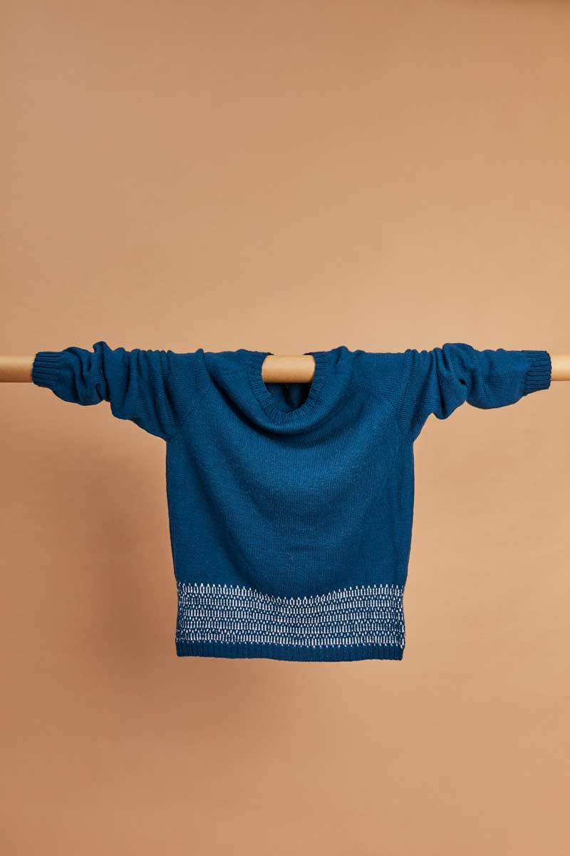 Bellish raglan sweater hanging draped over rail