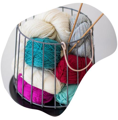 Yarn skeins and needles in wire basket bellish