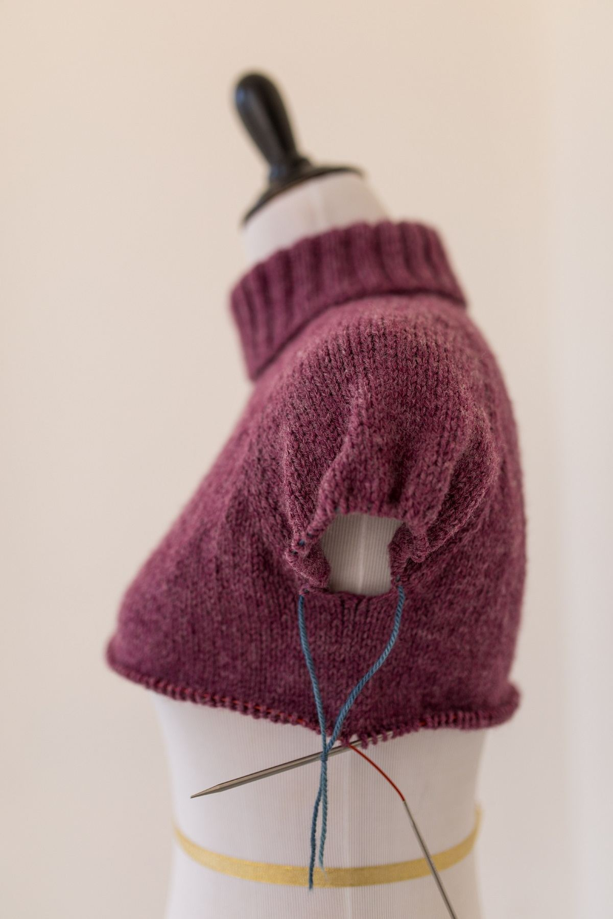 Side view sweater in progress on a mannequin