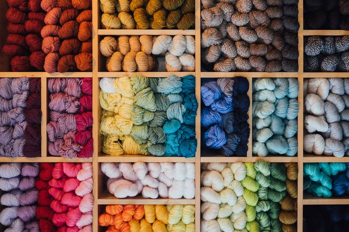Wall of colorful yarns on wooden shelves.