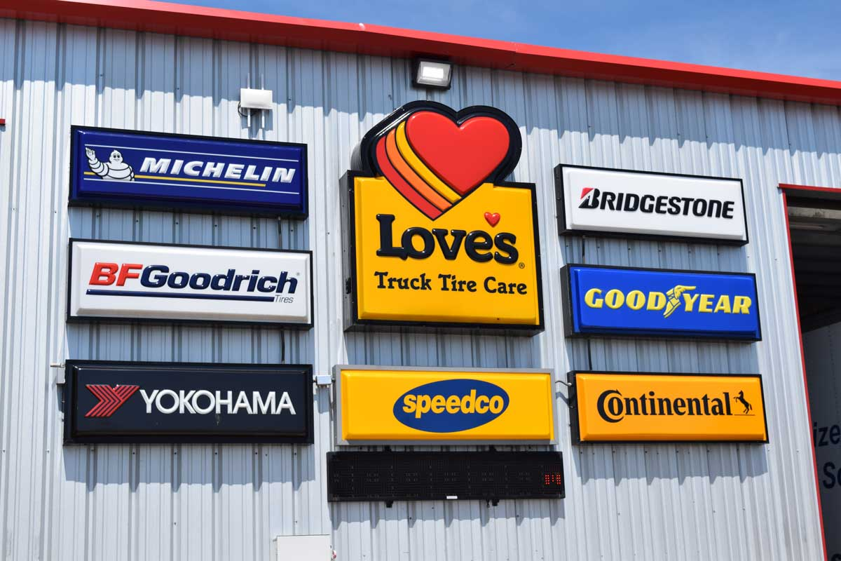 A college of tire brand signs installed at a Loves service center
