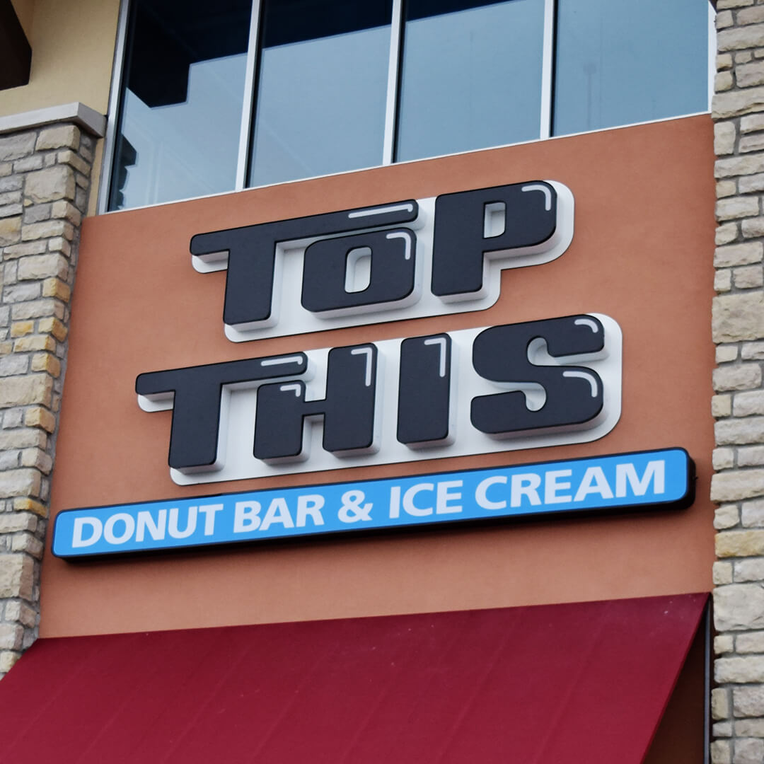 A trendy and simple sign design for Top This. This sign inverts between black and white. Black during the day and bright white during the night using special UV printing and lighting techniques.