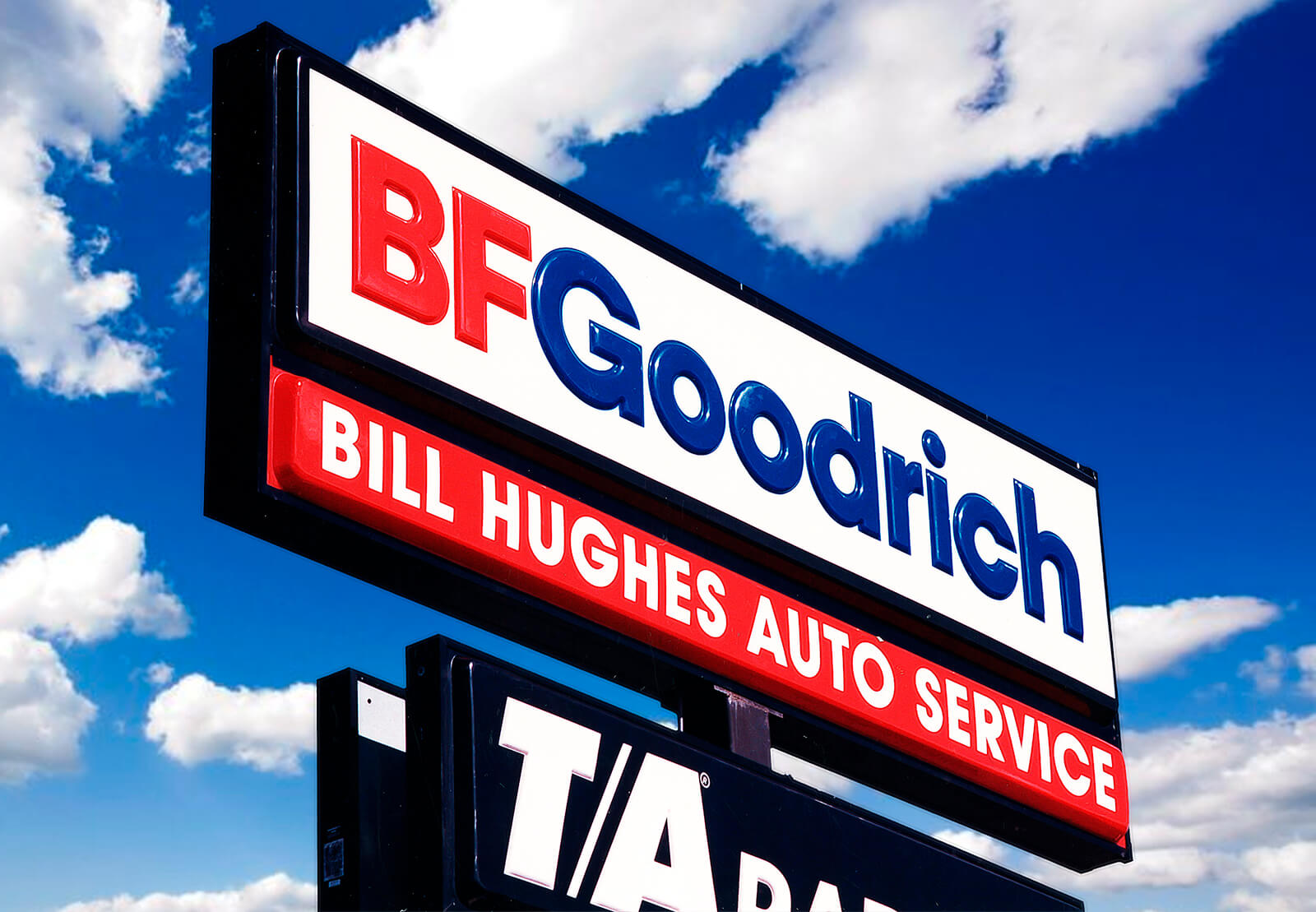 A massive sky high BFGoodrich sign with a custom franchise auto service name.