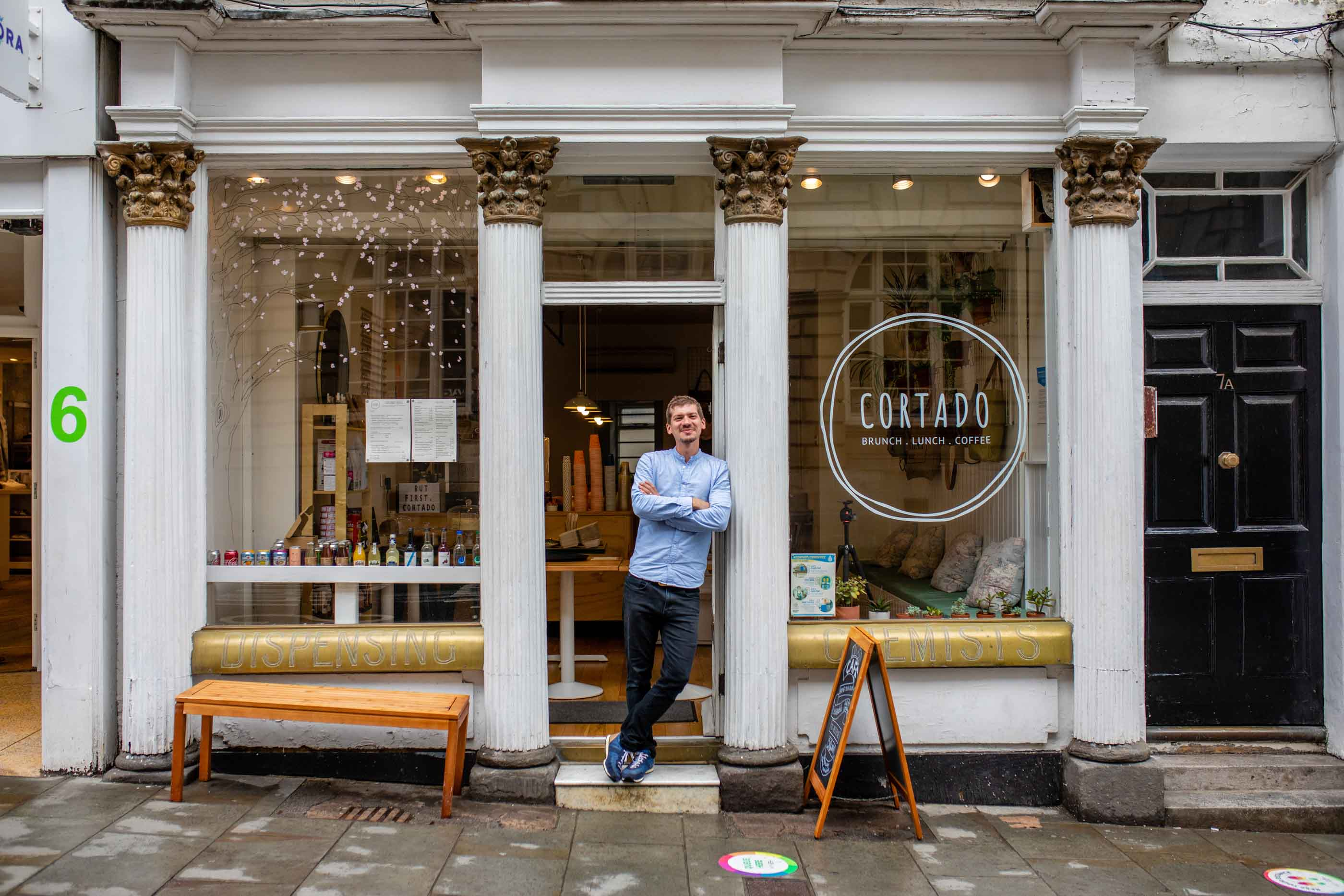 Fran, Owner of Cortado, Bath, standing outside his coffee shop.