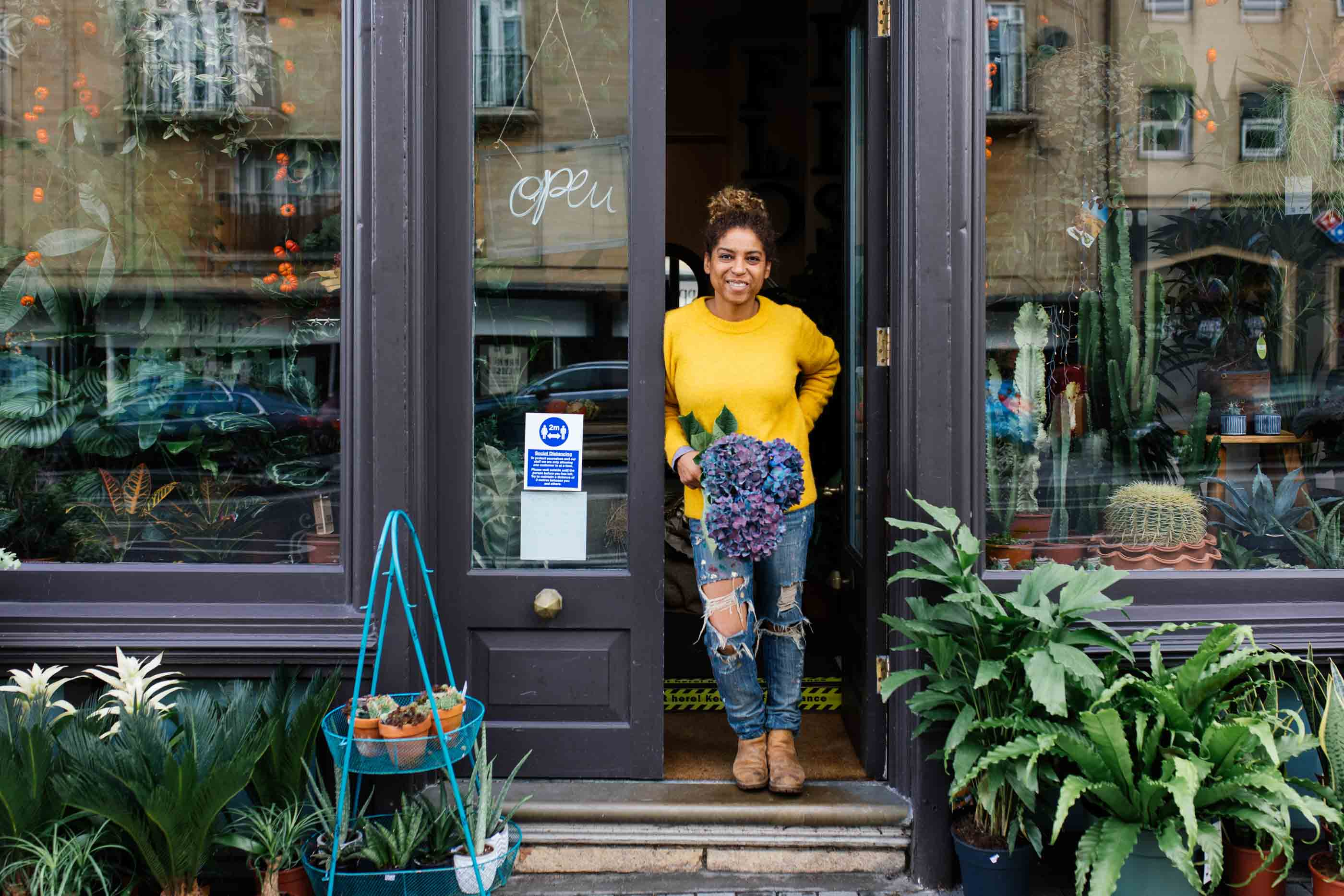 Marcia, owner of Flores by M Wood, Bath, standing out side her flower shop