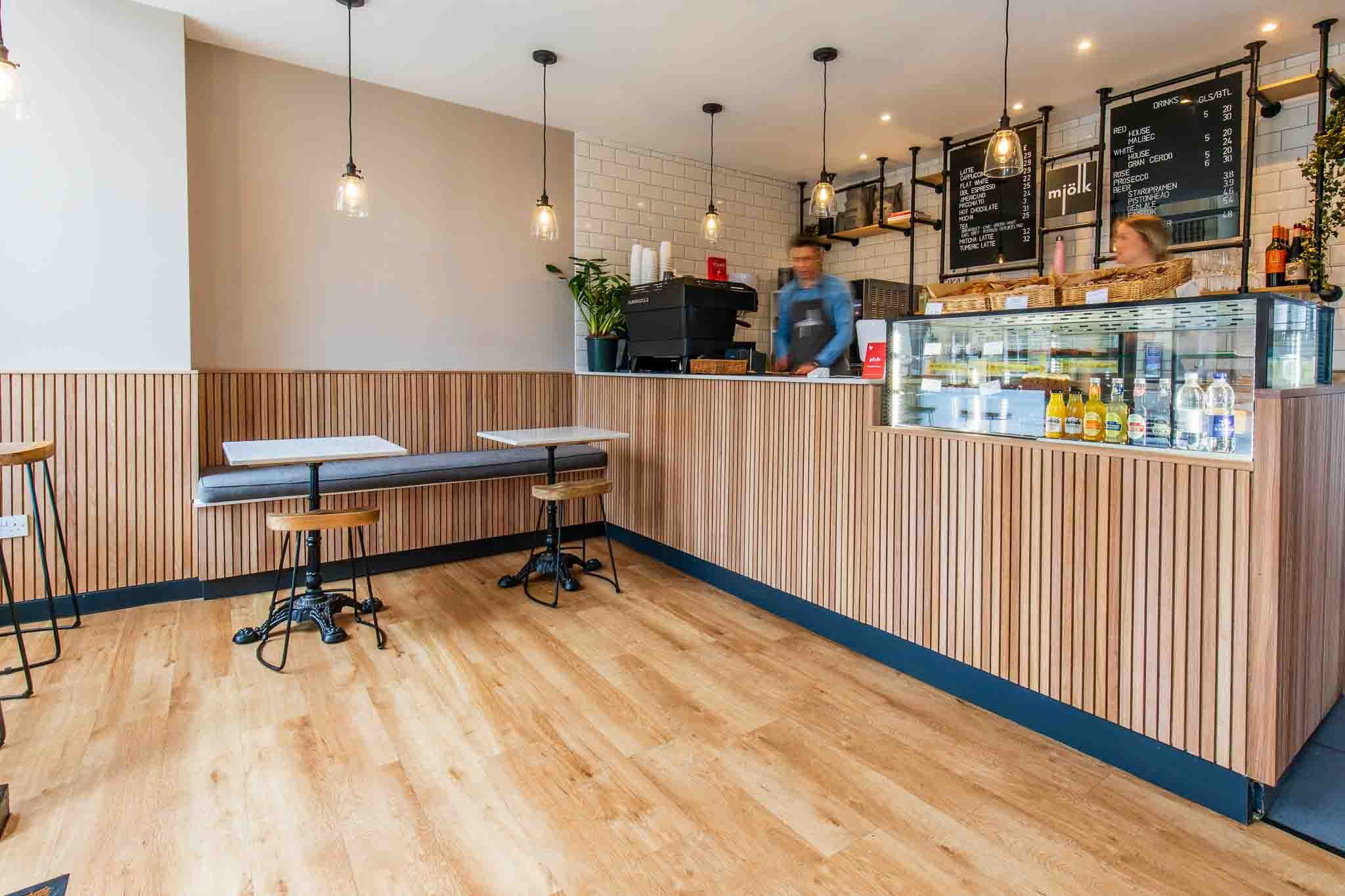 Professional photograph of a cafe, showing improved lighting, space and action.