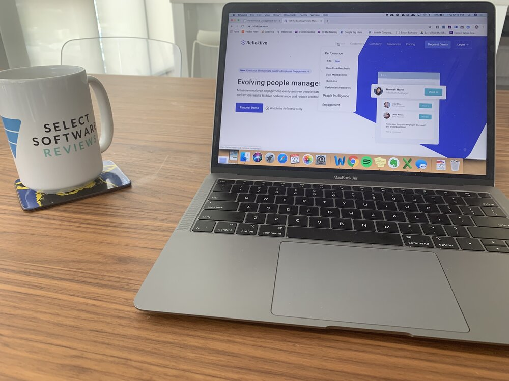 Viewer enjoying coffee in a SelectSoftware Reviews mug and looking at Reflektive software demo screen on computer