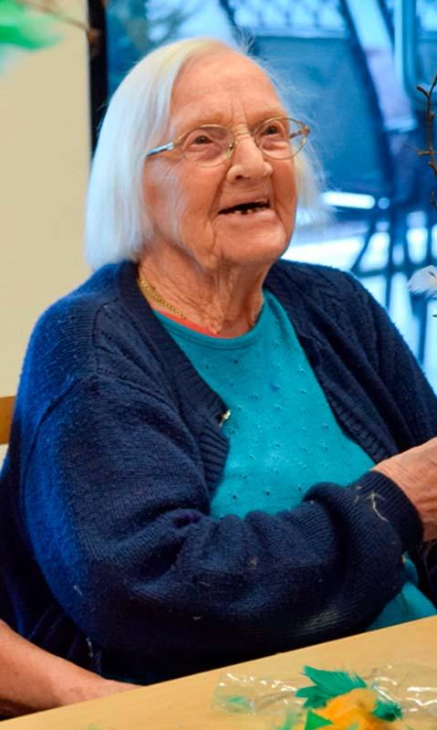 En eldre dame i blå genser smiler