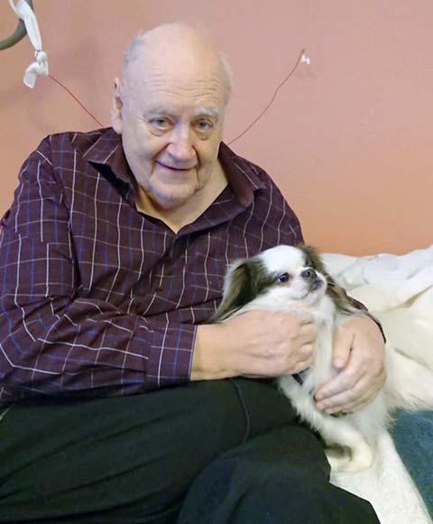 En eldre mann koser med en besøkshund