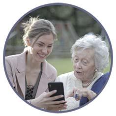 Eldre dame og en kvinne bruker appen Triggo på mobilen
