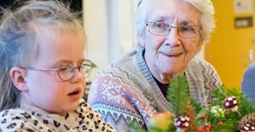 Eldre dame og et barn lager julepynt