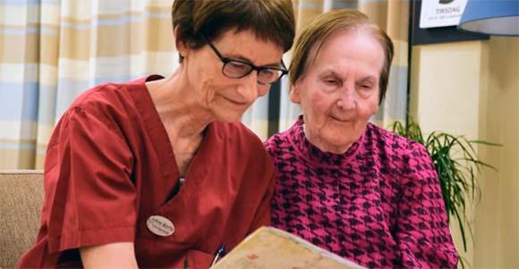 Helsepersonell og beboer på et sykehjem har en fin stund