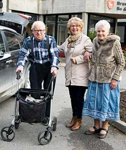 Eldre dame går tur med to beboere på sykehjem