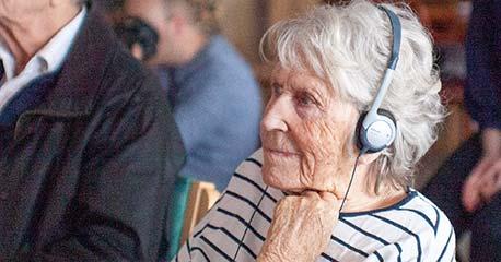 Eldre dame med hodetelefoner ser på video gjennom Televindu