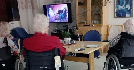 Eldre personer har en fin stund sammen på fellesstua med video gjennom Televindu