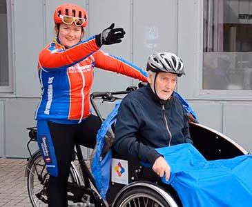 En dame som skal starte elsykkelturen med en eldre person foran på sykkelen