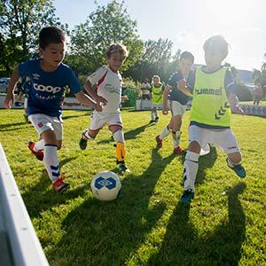 Barn spiller fotball i fint vær