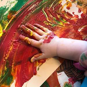 Barnehånd som maler et fargerikt maleri uten pensel