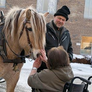 Mann holder en hest slik at en dame i rullestol får hilse på hesten