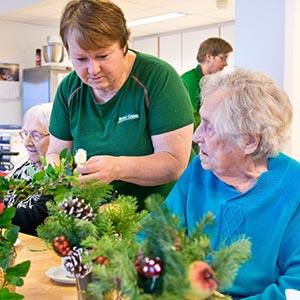 Ansatt i blomsterbutikk viser en eldre dame blomsteroppsatser