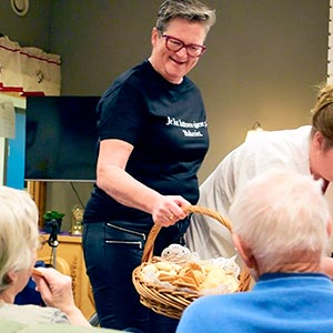 Blid dame som serverer fersk bakst til sykehjemsbeboere