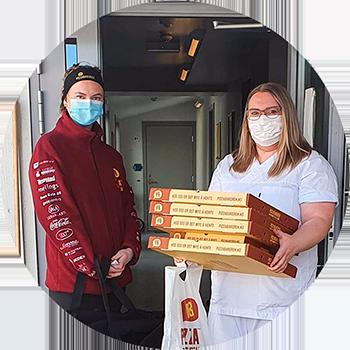Omsorgsansatt og ansatt fra en pizzarestaurant med ferske pizzaer