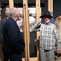 Tre eldre menn besøker et museum