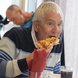 Eldre mann spiser pizza til middag